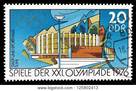 GERMAN DEMOCRATIC REPUBLIC- CIRCA 1976 : Cancelled postage stamp printed by German Democratic Republic, that shows town hall and gymnasium.