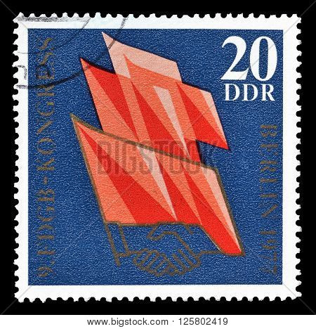 GERMAN DEMOCRATIC REPUBLIC - CIRCA 1977 : Cancelled postage stamp printed by German Democratic Republic, that shows flags and handshake.