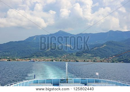 Beautiful moment from a summer trip to the island of thassos, greece, forested mountains,sky with clouds, house with a red tile roof, the rear of the ferry, a trail on the water from a floating ferry