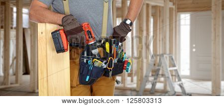Builder handyman with drill and wooden plank.