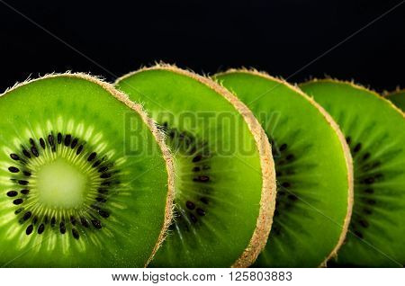 cut slices of kiwi fruit close-up on black background horizontal. space for text