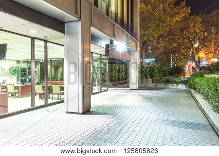 portland,usa: modern office building and empty brick footpath at night by zhu difeng on Nov,11,2015