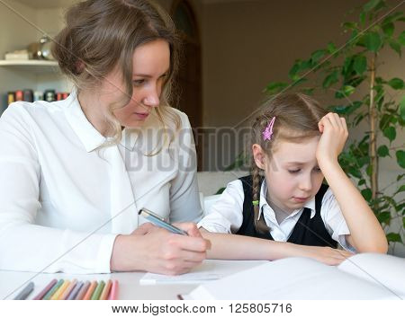 Mother Helping Her Tired Daughter With Homework At Home.