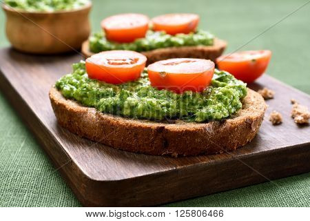 Sandwiches with pesto sauce and tomatoes close up view