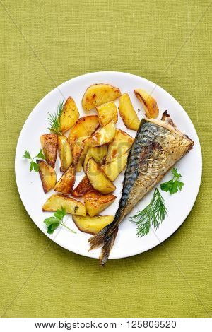 Roasted potato wedges and mackerel fish top view
