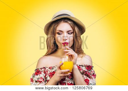 Pretty young woman drink orange juice. Girl in hat and sweet summer dress on yellow background