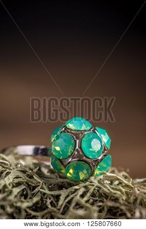 Ring with rhinestone on brown background, studio shot
