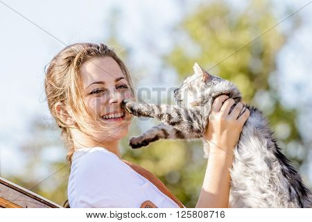 outdoor portrait of young happy woman with cat on natural background on farm