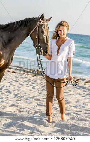 Beautiful woman on a horse. Horseback rider, woman riding horse, sea background