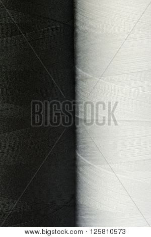 two black and white spools of thread close-up