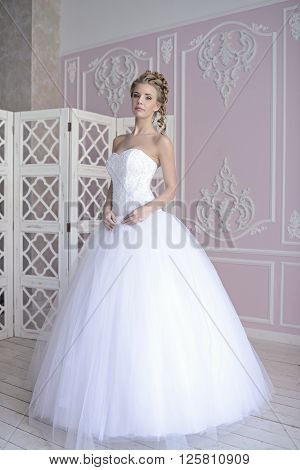 Beauty bride in bridal gown indoors. Beautiful model girl in a white wedding dress