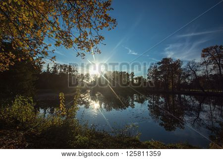 Sunset over the pond. Trees are reflected in the lake. Autumn color landscape