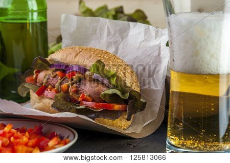 hotdog with sausage tomato and lettuce beer bottle and glass. Fast food. Selective focus.