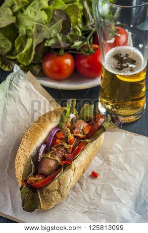 Hotdog with sausage and vegetables and glass of beer. fast food. Selective focus.