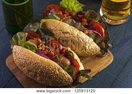 Two hotdogs with sausages and vegetables beer bottle and glass on wooden table. Fast food.