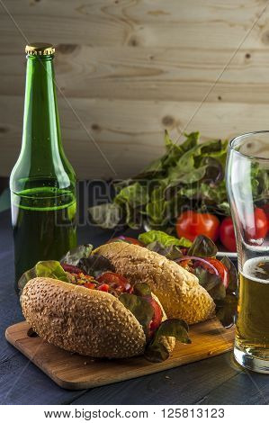 Hotdogs with vegetables and lettuce and beer bottle and glass on wooden table.