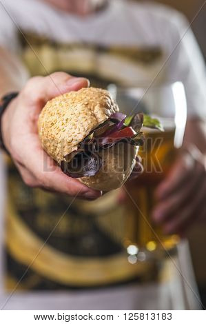 Hotdog and glass of beer in man's hands. fast food and alcoholic drink. Selective focus. ** Note: Shallow depth of field