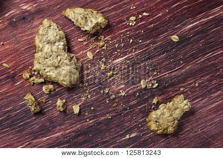 Oatmeal cookies crumbs on wooden table closeup.