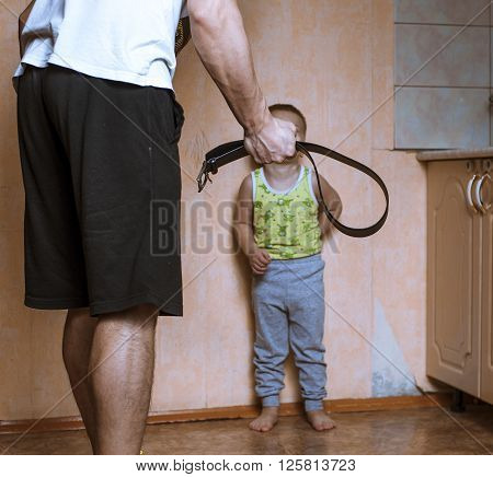 Home violence: Angry father with belt and scared child
