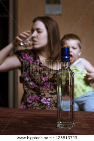 Drunk woman with alcoholic drink and crying child. Female alcoholism. Focus on bottle.