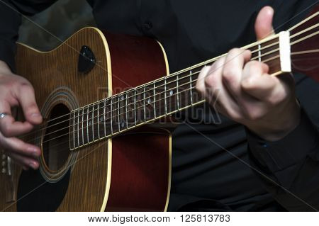 Closeup of man's hands playing on guitar