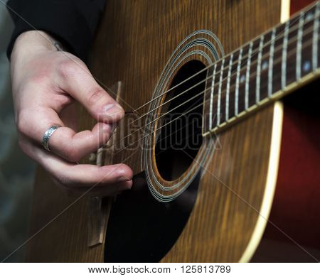 Acoustic guitar in male hands, closeup. Horizontal view