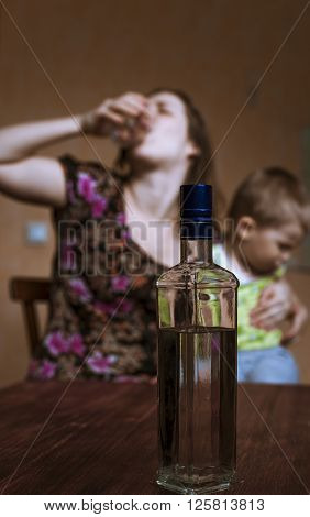 Family problems: Drunk mother with alcohol and little son. Alcoholic addiction. Focus on bottle.