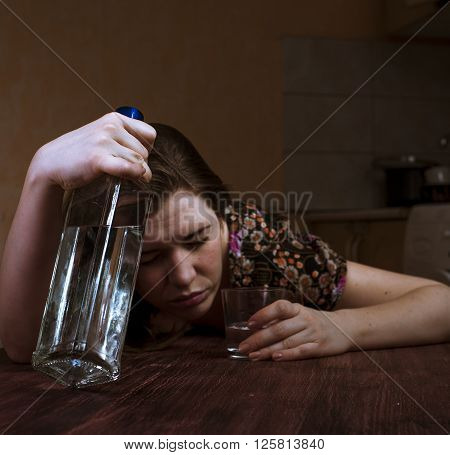 Lonely woman holding alcohol bottle and glass. Portrait of drunk woman.