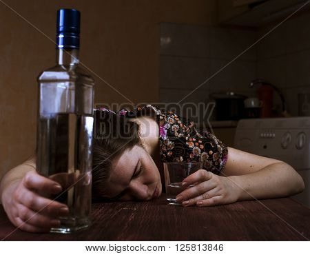 Tired drunk woman sleeping on the table and holding her glass. Focus on hand with glass.