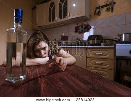 Drunk depressive woman holds empty glass and looks at the bottle with alcohol. Female alcoholism.