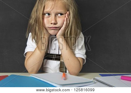sad and tired cute junior schoolgirl with blond hair sitting in stress working doing homework looking bored and overwhelmed in children education at school and academic performance