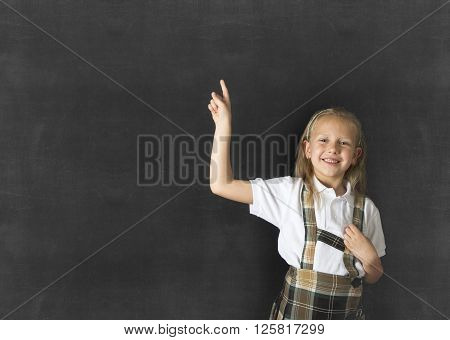 young sweet junior schoolgirl with blonde hair standing and smiling happy pointing to copy space on class blackboard wearing school uniform in children education success and fun