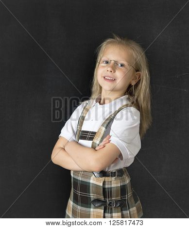 young sweet junior schoolgirl with blonde hair standing and smiling happy isolated in blackboard background wearing school uniform in children education success and fun