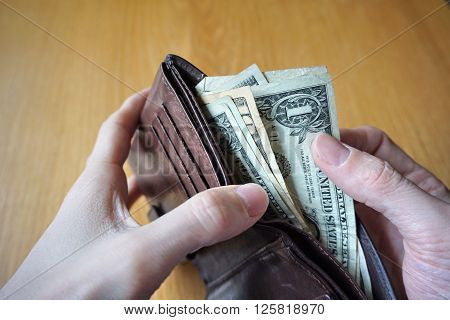 Male hand holding a leather wallet and withdrawing American currency (USD, US Dollars)