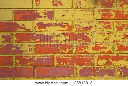 Red Brick Wall With Flakes Of Yellow Paint
