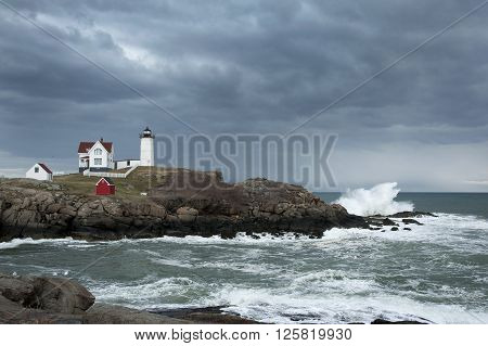 Storm clouds over Nubble lighthouse as waves crash on Maine's rocky coast.