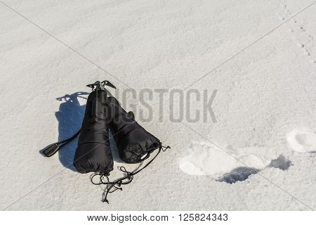 Ice Axe With Mittens On Snow.