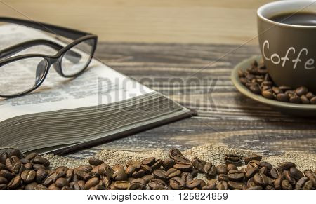 A cup of coffee with scattered coffee beans and open book with eyeglasses are stands on a piece of burlap. Focus on beans on burlap