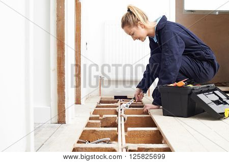 Female Trainee Plumber Fitting Central Heating System