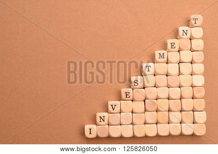 Wooden stairs with the word investment financial upswing concept on a cardboard background
