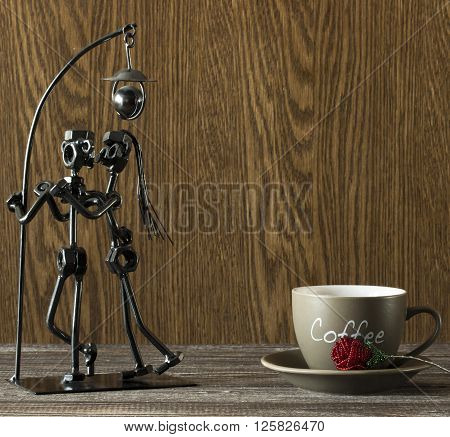 Statuette of a loving couple kissing under a lamp made of metal screws and rods next to a cup of coffee and artificial rose beads