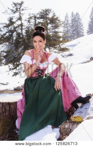 Very beautiful woman in a fashionable Dirndl sitting on a tree stump in the spring surrounded by snowfields and enjoys the first rays of spring