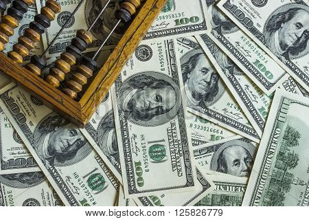 Background texture of banknotes in denominations of one hundred dollars scattered on a table and an old wooden abacus