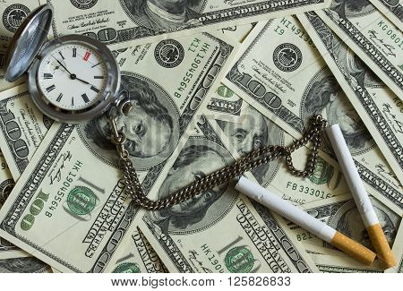 Background texture of banknotes in denominations of one hundred dollars scattered on a table and an old pocket watch with two cigarettes
