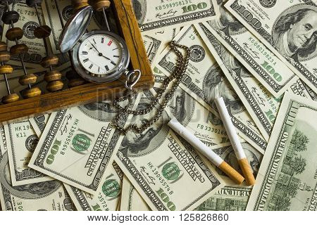 Background texture of banknotes in denominations of one hundred dollars scattered on a table and an old pocket watch with two cigarettes and old wooden abacus