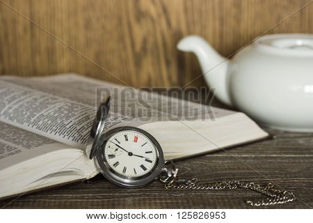 Open book on which lie the old vintage pocket watch with chain and white ceramic teapot. Focus is on the clock