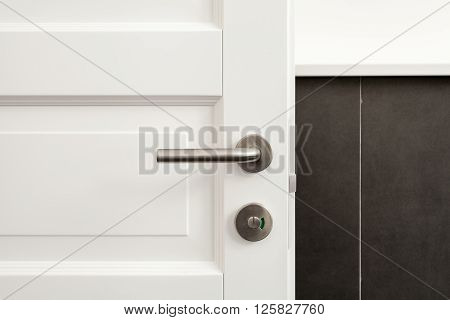 Open white door with metallic handle close up