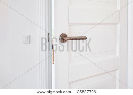 White door with metal handle close up