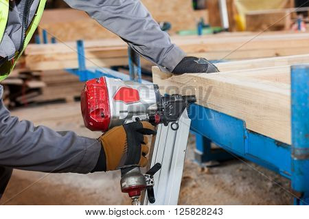 Building a wall for frame house.Worker use Framing Nailer to attach wooden beams