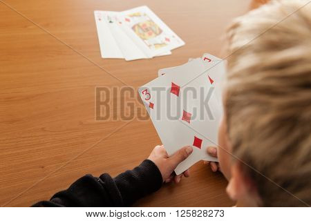 Over The Shoulder View Of Child Playing Cards